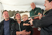 """Kylie Preisinger, of Fort Bragg, N.C., introduces her step-father Craig Wortman, mother Joan Wortman, and daughter Caroline, 1, as auctioneer Ron Wright stands by at the start of the Green Acres herd dispersal sale in South Randolph, Vt., Saturday, May 14, 2016. """"At least we're doing it for a good reason,"""" said Preisinger, who served on the board of the American Shorthorn Association until June 2016. """"We're doing it on our own terms,"""" she said of the sale that will allow her parents to retire from farming. (Valley News - James M. Patterson) Copyright Valley News. May not be reprinted or used online without permission. Send requests to permission@vnews.com."""