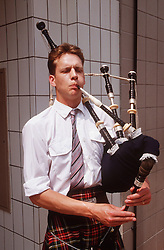 Man standing in street wearing traditional Scottish clothing playing bagpipes,