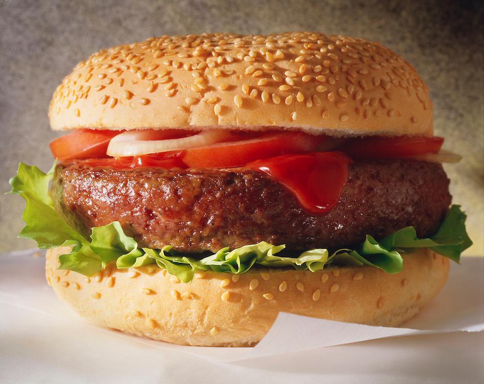 Photo of classic hamburger in sesame bun with Ketchup & Salad. Funky Stock Photos.