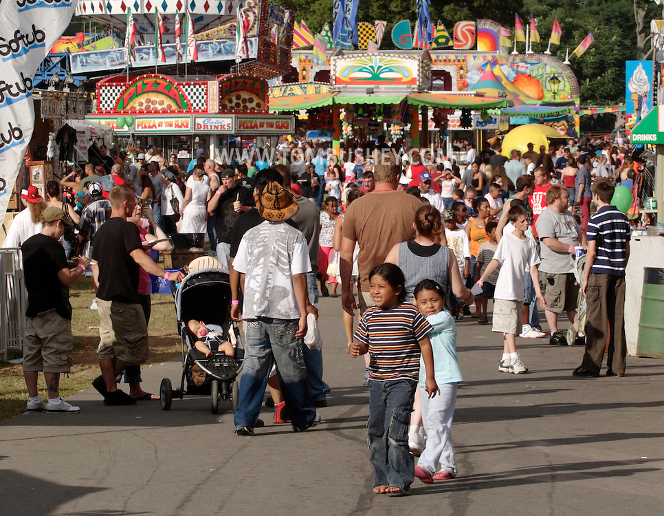 New Paltz, NY - Crowds of people walk past rides and carnival games at the Ulster County Fair on Aug. 3, 2008.