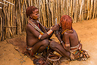 Hamer woman applying a mixture of goat butter and red ocher (clay earth) that gives the bright red color and keeps their dreadlocks neatly in place. Omo Valley, Ethiopia.