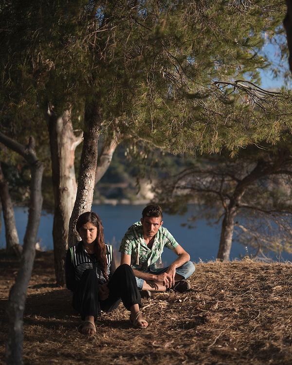 Yazidi refugees Hazim Elias Khadeda, 22, and his sister Leena Elias Khadeda, 16, sit among the pines beside the sea at Lakki.