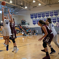 Odessa Begay (12) of Miyamura scores on a layup against Belen defenders in Gallup on Saturday. The Lady Patriots won 63-34.