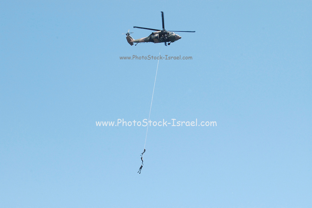 Military helicopter rescuing three frogmen out of the sea