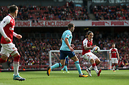Hector Bellerin chips the ball over a Bournemouth defender to teammate  Mesut Ozil (l) . Premier league match, Arsenal v AFC Bournemouth at the Emirates Stadium in London on Saturday 9th September 2017. pic by Kieran Clarke, Andrew Orchard sports photography.