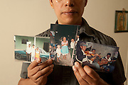 Victor Hernandez with photos of his family in Mexico. His maternal uncle is playing the fiddle in the photo on the right.