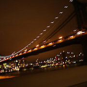 An image from a car traveling past bridge and city landmarks showing motion and movement as it navigates through the city lights and metropolis of the big city at night time. New York, USA. 26th October 2012. Photo Tim Clayton