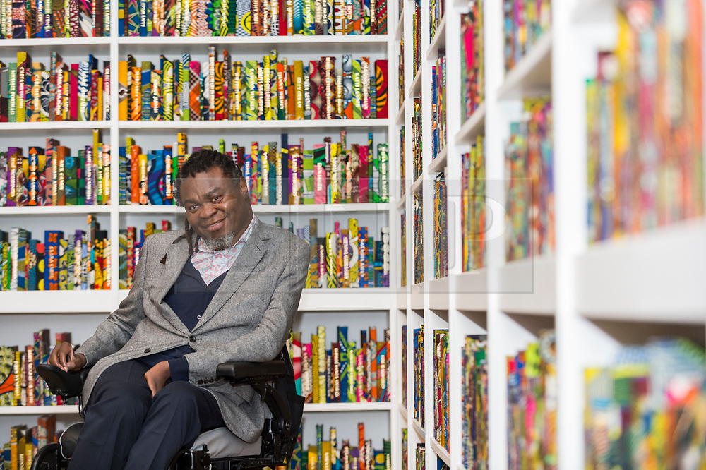 """© Licensed to London News Pictures. 08/04/2019. LONDON, UK.  British-Nigerian artist Yinka Shonibare poses at a photocall with his work """"The British Library"""", 2014, which has been acquired by Tate Modern.  Comprising 6,328 books, covered in wax fabric and gold foil, 2,700 books have the names of first or second generation immigrants to Britain on the spine.  Photo credit: Stephen Chung/LNP"""