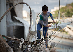 A nine-year-old Palestinian boy plays in the rubble, after part of his family home has been demolished in the Shu'fat village in Jerusalem. As building permits are notoriously difficult, in some cases impossible, for Palestinians to obtain, demolition of houses stated not to have the relevant permits is common in the area. This time, the family lost their living room, two bathrooms, and kitchen.