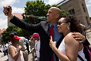 20 MAY 2018 -- ST. LOUIS -- US Sen. Cory Booker (left), D-NJ, poses for a selfie with Rita Griffin of UAW Local 2250 before the start of the 2018 Annie Malone May Day Parade on Market Street in downtown St. Louis Sunday, May 20, 2018. The parade benefits the Annie Malone Children & Family Service Center, which has been assisting families in St. Louis for 130 years. Photo © copyright 2018 Sid Hastings.
