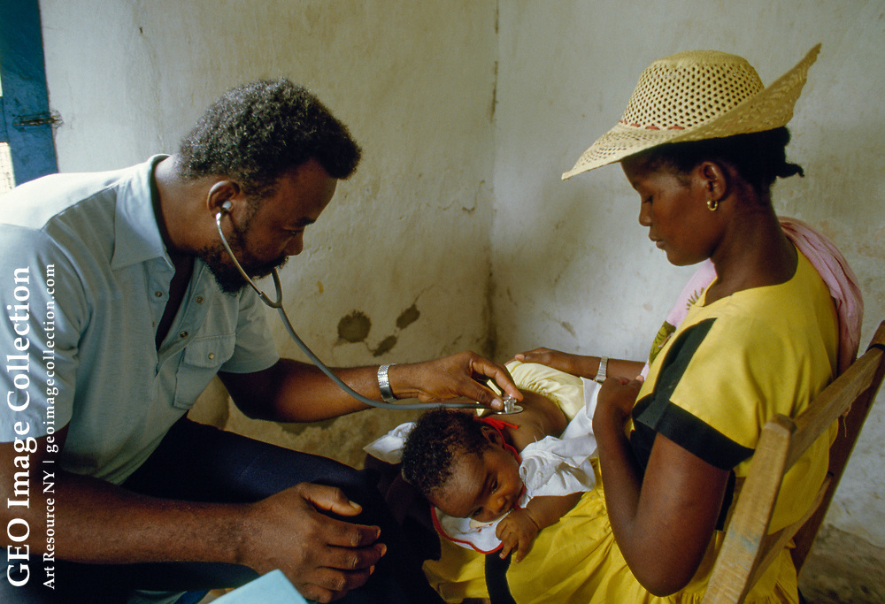 Ketelie Regis, a 22-year-old mother of three, watches as a doctor examines her youngest child.