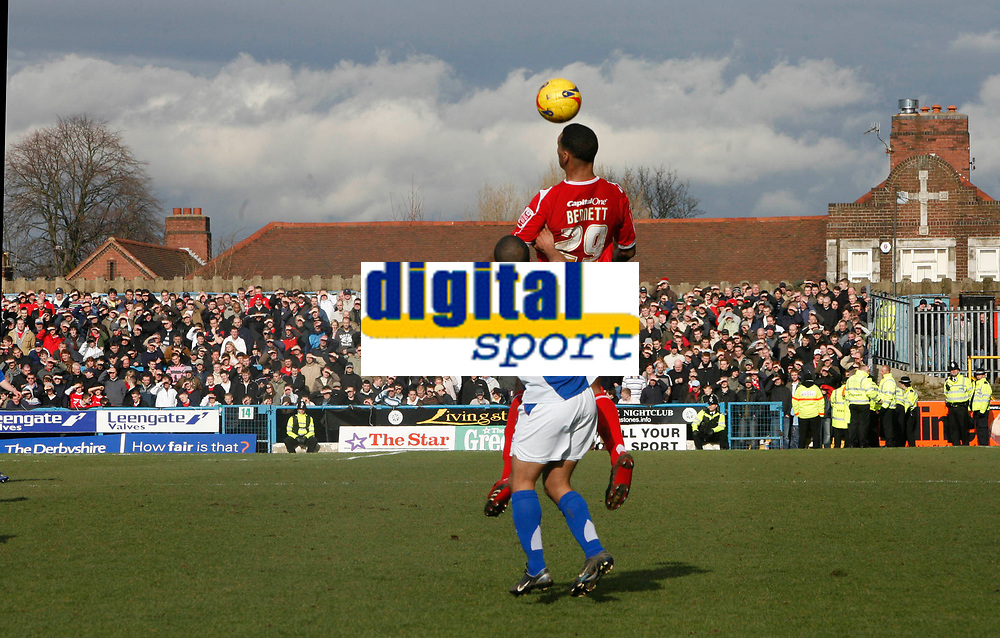 Julian Bennett of Forest rises above Alex Bailey of Chesterfield in front of the away fans