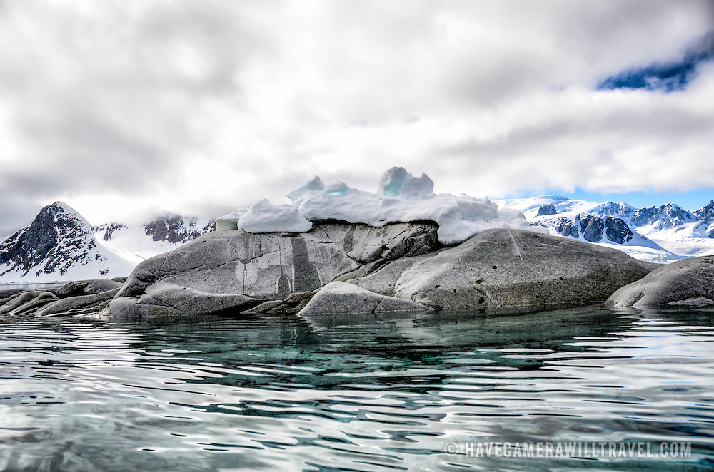 Smooth gray rocks stick out of the clear waters of Petermann Island on the Antarctic Peninsula.