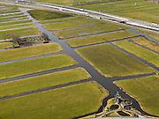 Nederland, Zuid-Holland, Gemeente Alkemade, 20-02-2012; infrastructuur bundel bestaande uit autosnelweg A4 en het hogesnelheidspoor HSL-Zuid. De verdiepte kruising HSL- A4, met viaduct van de hogesnelheidslijn over de lager gelegen snelweg. Veenweidelandschap bij Rijpwetering, met waterwipmolen..Infrastructure bundle consisting of A4 motorway and the high speed rail HSL. The HST crosses the recessed motorway junction..luchtfoto (toeslag), aerial photo (additional fee required).copyright foto/photo Siebe Swart