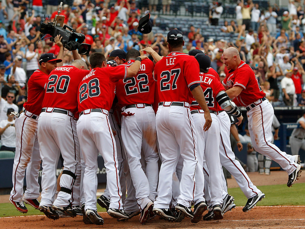 ATLANTA - AUGUST 29:  Members of the Atlanta Braves mob catcher Brian McCann #16 (not pictured) after McCann's game winning home run against the Florida Marlins at Turner Field on August 29, 2010 in Atlanta, Georgia.  The Braves beat the Marlins 7-6.  (Photo by Mike Zarrilli/Getty Images)