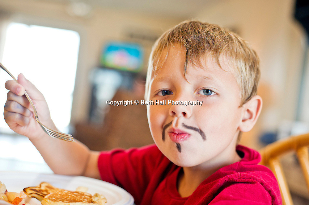 A boy eats breakfast after playing dress up and painting a mustache on his face.