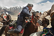 Whip in mouth, a Kyrgyz man steers his horse in a game of Buzkashi, a competition akin to polo?except a headless goat carcass takes the place of the ball. .Buzkachi is almost exclusively played during weddings..Probably one of the great pleasures in the life of a Kyrgyz man, Buzkashi is Afghanistan's national sport. The Kyrgyz call it ulak tartysh, or ?goat grabbing.?..Wedding celebration at Kitshiq Aq Jyrga...Trekking through the high altitude plateau of the Little Pamir mountains (average 4200 meters) , where the Afghan Kyrgyz community live all year, on the borders of China, Tajikistan and Pakistan.