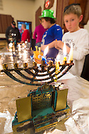 The Merrick Jewish Centre attempts to regain the Guinness World's Record for Most Menorot Lit in One Place at One Time that the congregation held in 2011. A young boy looks at a menorah with doors that open to reveal Hebrew writing, which Ann Liss of Woodmere brought, on the third night of Hanukkah, to the 'Light Up the Night 2 - Bringing the Record Home' event.