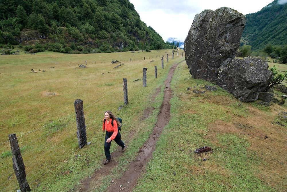 Woman hiking through farmland in Chile's Futaleufu River Valley.