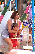 Mom and son slinging water balloons at Grand Old Day age 33 and 4.  St Paul  Minnesota USA