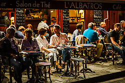 People enjoying a drink in a cafe around the harbour in Honfleur, France