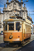 The heritage tram line with brown vintage tramcar driving along its historic route right next to Gothic Church of Our Lady of Mount Carmel (Igreja do Carmo), Porto, Portugal Ⓒ Davis Ulands | davisulands.com
