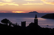 The Islet of Bicevo seen from Vis, with its monastery silhouetted,  as the sun sets over the Adriatic Sea.