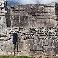 A man cleaning and restoring a wall of Machu Picchu.