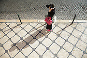 A lady talks on the phone on top of typical portuguese limestone paved sidewalks.