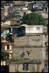 CAP HAITIEN, HAITI - A man exercises on the roof of one of the many one-room shanties dotting the Cap Haitien landscape, where most families live without electricity, running water, and indoor plumbing.(PHOTO © JOCK FISTICK)....