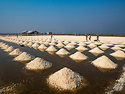 10 FEBRUARY 2016 - BAN LAEM, PHETCHABURI, THAILAND: Salt stacked in piles in a salt field at the beginning of the harvest in Phetchaburi province, Thailand. The salt harvest in Thailand usually starts in February and continues through May. Salt is harvested in many of the provinces along the coast, but the salt fields in Phetchaburi province are considered the most productive. The salt fields are flooded with sea water, which evaporates off leaving salt behind. Salt production relies on dry weather and producers are hoping the current drought will mean a longer harvest season for them.      PHOTO BY JACK KURTZ