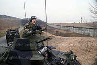British army reconnaissance patrol along the East/West German border of the Berlin Wall in 1979. In the foreground a sergeant watches from his Ferret Armoured car. In the background a modified landrover follows. Photograph by Terry Fincher