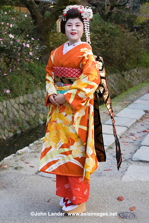 Maiko, an apprentice Geisha, posing along the Tetsugaku-no-Michi or The Path of Philosophy. This two-kilometer path which follows a canal, runs from Ginkaku - ji Temple to Wakaoji-Shrine. Cherry and maple trees line the small canal forming a tunnel of cherry blossoms in the spring and colorful maple leaves in the fall.