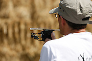 Photo by Andrew Tobin/Tobinators Ltd - 07710 761829 - Richard Marsden of Haddenham takes aim with his laser sighted pea shooter during the World Peashooting Championships held at Witcham, Cambridgeshire, UK on 13th July 2013. Run in conjunction with the village fair, the Championships have been held in Witcham since 1971 when they were started by a Mr Tyson, the village schoolmaster, in order to raise funds for the village hall.Competitors come from as far afield as the USA and New Zealand to attempt to win the event. The latest technology is often used, including laser sights and titanium and carbon fibre peashooters. All peashooters must conform to strict length rules, not exceeding 12 inches, and have to hit a target 12 feet away. Shooting 5 peas at a plasticine target attached to a hay bale, the highest scorers move through the initial rounds to a knockout competition, followed by a sudden death 10-pea shootout.