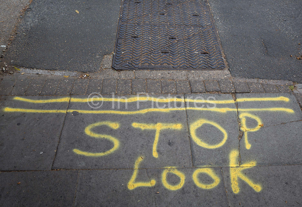 The words STOP and LOOK sprayed on to the pavement where cars cross the pavement near Kings College Hospital in Camberwell, on 5th July 2018, in London, England.