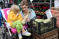 Mother with toddler in buggy choosing vegetables