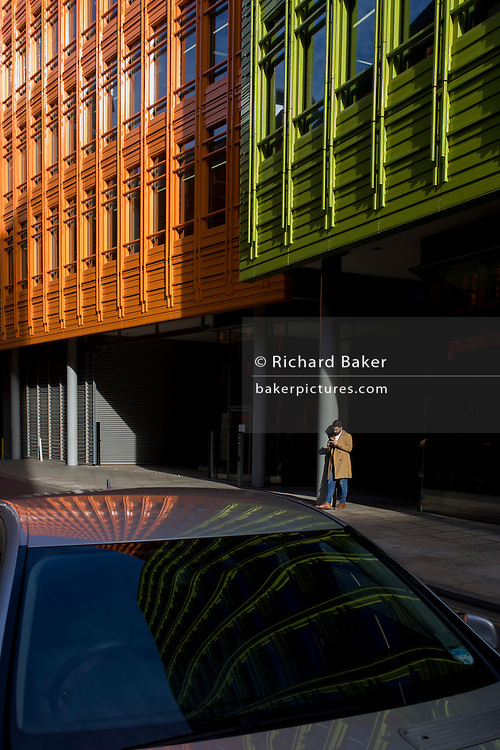 Man uses smartphone beneath modern architecture at Central Saint Giles in central London.