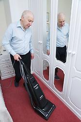 Older man hoovering in the bedroom,