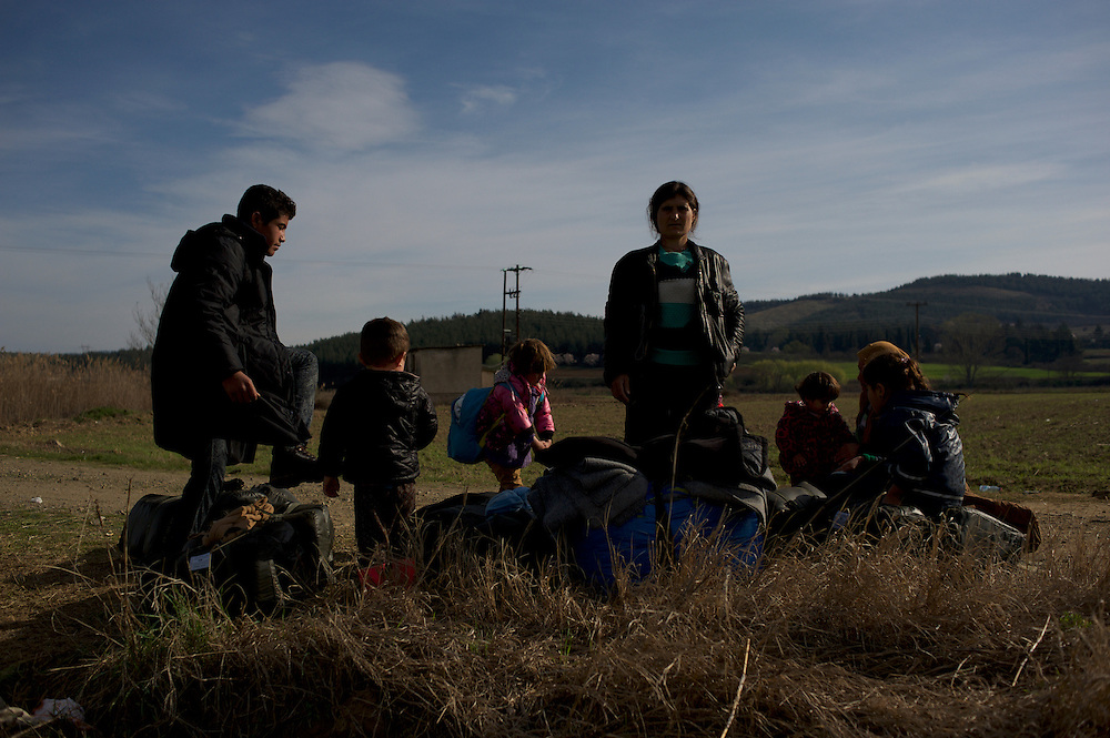 A group of Kurdish-Syrian refugees take a rest in a field during their journey towards the Greek-Macedonian border station of Idomeni, Greece.