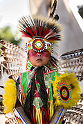 A young Native American dancer from the Arapahoe people dressed in traditional costume prepares to perform a fancy dance at the Indian Village during Cheyenne Frontier Days July 25, 2015 in Cheyenne, Wyoming. Frontier Days celebrates the cowboy traditions of the west with a rodeo, parade and fair.