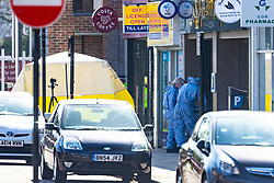 A large cordon surrounds the scene in Marsh Road, Pinner, West London, as police and forensics officers investigate the murder of a man outside an off licence. London, March 24 2019.