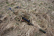 Lying in undergrowth, a camouflaged British infantry soldier is seen looking down the telescopic sight of the new British-made Long Range L115A3 sniper rifle on Salisbury Plain, Warminster, England. Sniping means concealment, observation and assassination, a strategy the British are using more against the Taliban in Afghanistan. Swiss Lapua .338 inch rounds (8.59mm) travel at sub-sonic speeds of 936 metres/sec, finding its target accurately up to 1,100 metres. The rifle weighs 6.8kg with telescopic image-intensified scopes to 25x life size vision, made by Schmidt & Bender. Front-mounted 'suppressor' minimises the signature normally compromising snipers' position. At £23,000 each, a £4 million contract has been awarded to Accuracy International, to provide the Army, Royal Marines and RAF. The British say this is the best sniper rifle in the world.