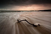 A piece of driftwood jammed in the sand at Silver Bay, Anglesey get washed by incoming waves in the cove at sunset, during stormy, wet weather.