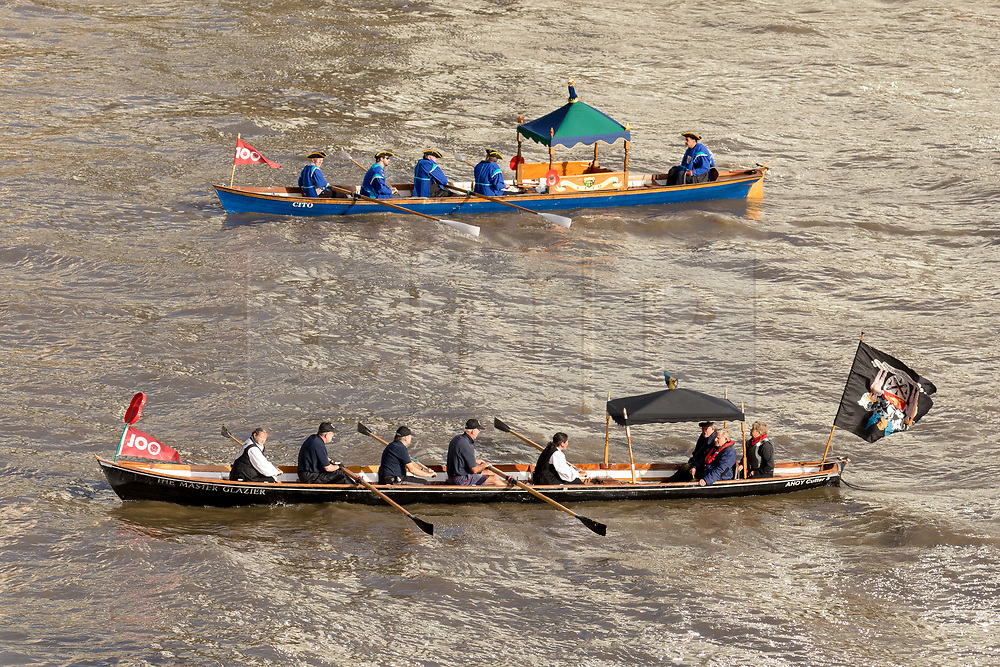 © Licensed to London News Pictures. 11/11/2018. London, UK.  Two small traditional vessels with a 100 centenary flag is rowed amongst a flotilla of boats including the Royal barge, QRB Gloriana, the Havengore and traditional boats travel up the River Thames towards the Houses of Parliament in Westminster for a remembrance service, led by the Havengore, as part of Armistice Day centenary events taking place in central London. Big Ben will strike at 11am to mark the start of the two minutes silence and the Havengore will sound her horn to signify the end of the two minutes silence in central London.  Photo credit: Vickie Flores/LNP