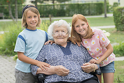 Senior woman on wheelchair with grandchildren at rest home park, Bavaria, Germany