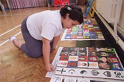 Primary school girl kneeling on floor in school hall arranging pupils' paintings into art display,