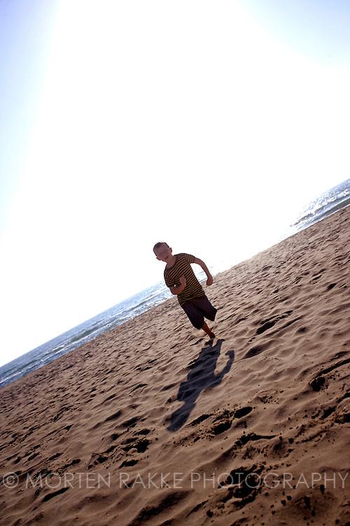 Boy running at beach, Italy