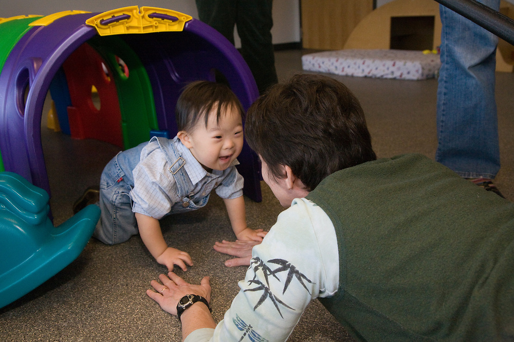 United States, Washington, Bellevue, baby crawling through tunnel to therapist  at Kindering Center