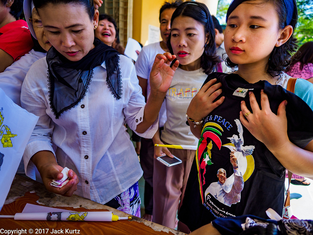 19 NOVEMBER 2017 - HWAMBI, YANGON REGION, MYANMAR: People buy tee shirts marking the Pope's visit to Myanmar at Sacred Heart's Catholic Church in Hwambi, about 90 minutes north of Yangon. Catholics in Myanmar are preparing for the visit of Pope Francis. He is coming to the Buddhist majority country November 27-30. There about 500,000 Catholics in Myanmar, about 1% of the population. Catholicism was originally brought to what is now Myanmar more than 500 years ago by Portuguese missionaries and traders.    PHOTO BY JACK KURTZ