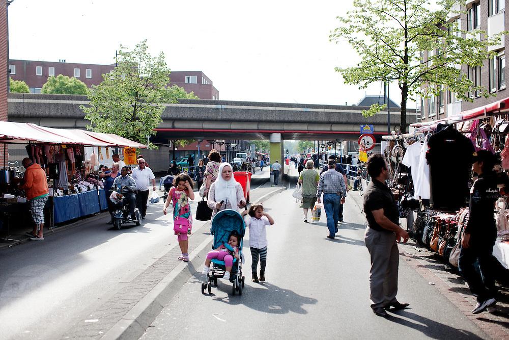Een vrouw loopt over de braderie op de Amsterdamsestraatweg in Utrecht.<br /> <br /> A woman is walking at the market on the Amsterdamsestraatweg in Utrecht.